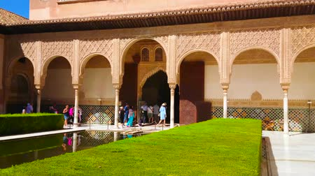 mór : GRANADA, SPAIN - SEPTEMBER 25, 2019: Tourists walk in shade of ornate arcade of Comares Palace and watch the scenic Court of Myrtles of Nasrid Palaces in Alhambra, on September 25 in Granada