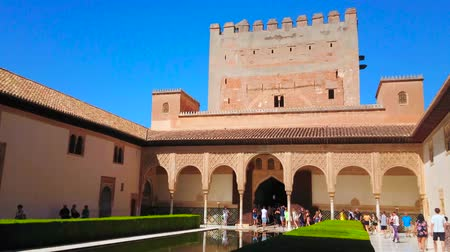 kolumna : GRANADA, SPAIN - SEPTEMBER 25, 2019: Historic Court of Myrtles (Nasrid Palace, Alhambra) with topiary myrtle bushes, big pond and arcade of Comares palace with Tower, on September 25 in Granada