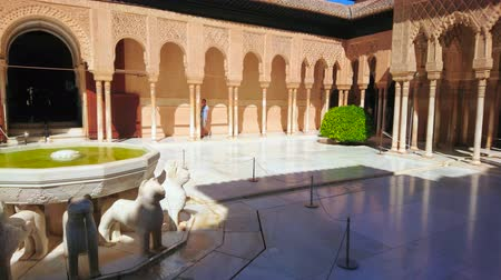kolumna : GRANADA, SPAIN - SEPTEMBER 25, 2019: Panorama of medieval Court of Lions (Nasrid Palace, Alhambra) with ornate arcade, decorated by pillars and sebka brick carvings, on September 25 in Granada
