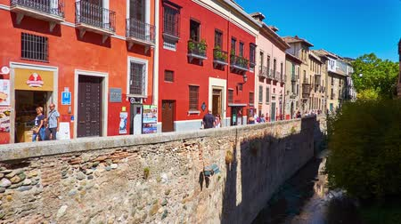 iberian : GRANADA, SPAIN - SEPTEMBER 25, 2019: The line of colorful medieval edifices at the bank of Darro river in Carrera del Darro street, Albaicin district of Old Town, on September 25 in Granada