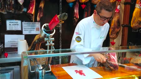 вылеченный : MALAGA, SPAIN - SEPTEMBER 26, 2019: The seller cuts Jamon Iberico (dry-cured Spanish ham) from the whole jamon leg, using special sharp knife, on September 26 in Malaga