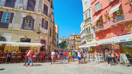рекламный : MALAGA, SPAIN - SEPTEMBER 26, 2019: The crowded noisy Plaza Carbon (square), lined with outdoor cafes, cozy bars and stores, located in historical edifices, on September 26 in Malaga