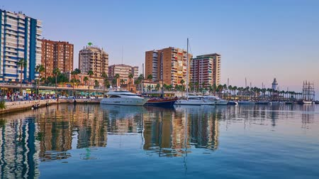 crepúsculo : MALAGA, SPAIN - SEPTEMBER 26, 2019: The evening walk in Malaga port with a view on Muelle Uno pier with moored yachts, line of cafes and modern high rises, reflected in sea, on September 26 in Malaga