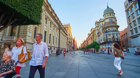 zasklený : SEVILLE, SPAIN - OCTOBER 2, 2019: People walk the busy Constitution Avenue with a view on historic Edificio la Adriatica, Bank of Spain building and riding modern trams, on October 2 in Seville