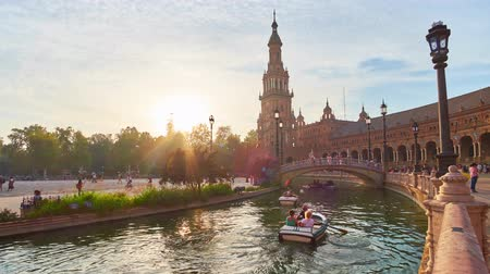 mudejar : SEVILLE, SPAIN - OCTOBER 2, 2019: Bright sunset over the trees of Maria Luisa Park with a view on splendid buildings, brdge and narrow canal of Plaza de Espana (Spain Square), on October 2 in Seville