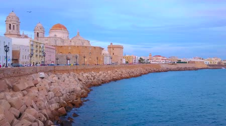 crepúsculo : CADIZ, SPAIN - SEPTEMBER 19, 2019: Panorama of evening Campo del Sur avenue with a view on ramparts, Cathedral, medieval Santa Cruz Church and coast of Atlantic Ocean, on September 19 in Cadiz
