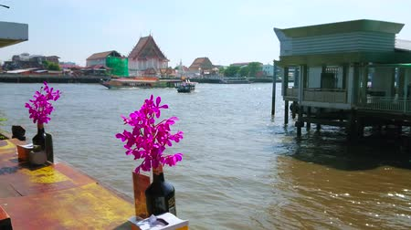 BANGKOK, THAILAND - APRIL 23, 2019: The outdoor riverside cafe with orchids in bottles on the tables overlooks the Chao Phraya with fast boats and ferries, on April 23 in Bangkok Stock Footage