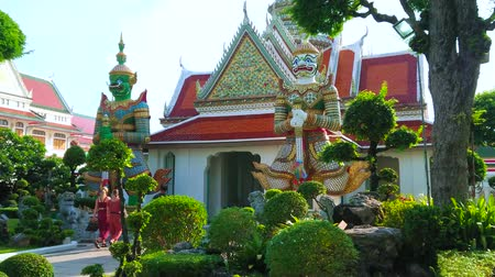 semt : BANGKOK, THAILAND - APRIL 23, 2019: The view through the topiary garden on spectacular Yaksha demon guardians gate of Wat Arun temple complex, on April 23 in Bangkok Stok Video