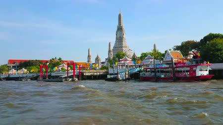 semt : BANGKOK, THAILAND - APRIL 23, 2019:  The ferry trip across the Chao Phraya river with a view on tall Prang tower of historical Wat Arun temple and pier, on April 23 in Bangkok Stok Video