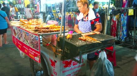 mercado : BANGKOK, THAILAND - APRIL 23, 2019: The street food stall of Khao San night market with grill cart, the seller cooks barbecue chicken, pork, saussages and puffs on skewers, on April 23 in Bangkok