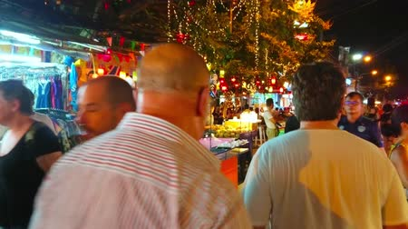 mercado : BANGKOK, THAILAND - APRIL 23, 2019: The crowded alley of Khao San night market, lined with cozy outdoor restaurants, bars, market stalls and massage salons, on April 23 in Bangkok