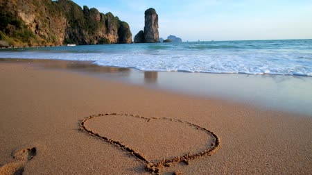 siamês : The waves wash away painted heart on the wet sand of Monkey beach with a view on scenic rocks on the background, Ao Nang, Krabi, Thailand
