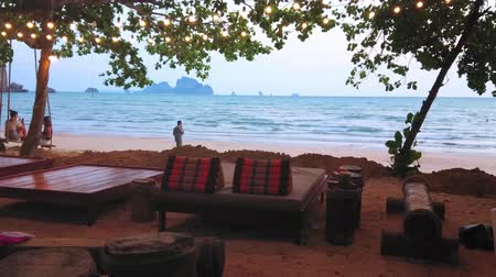 crepúsculo : AO NANG, THAILAND - APRIL 25, 2019: Evening relax in comfortable beach bar with line of sunbeds in shade of trees, on April 25 in Ao Nang