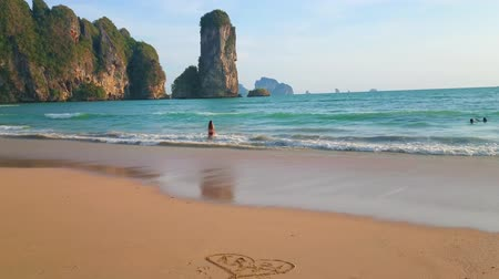 aonang : The coastline of Monkey beach with heart and Krabi inscription on the sand and the huge Ao Nang tower rock on the background, Krabi, Thailand Stock Footage
