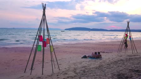 crepúsculo : AO NANG, THAILAND - APRIL 25, 2019: The evening Ao Nang beach with a view on colorful lanterns, hanging in bamboo stick construction, on April 25 in Ao Nang