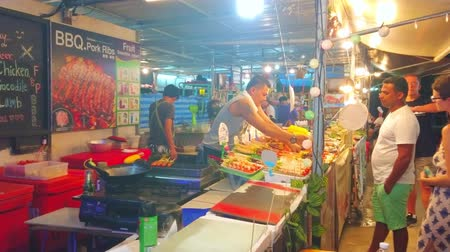 mercado : AO NANG, THAILAND - APRIL 25, 2019: The stall of the food court of Night Market with many foods on skewers, prepared on a grill, on April 25 in Ao Nang Stock Footage