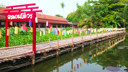ped : CHIANG MAI, THAILAND - MAY 4, 2019: The red decorative wooden gate and bamboo walkway on pond with lotus flowers and lily pads in park of Wat Chetlin (Jedlin, Jetlin) temple, on May 4 in Chiang Mai