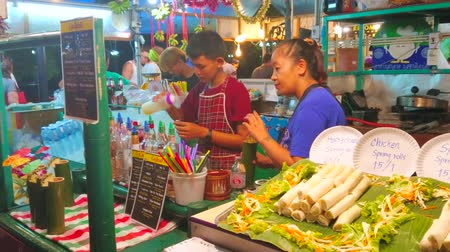 mercado : AO NANG, THAILAND - APRIL 25, 2019: Night Market attracts people with alcohol cocktails, served in  bamboo glasses with small umbrellas, orchid flowers and pieces of pineapple, on April 25 in Ao Nang