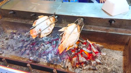 Rotisserie with spicy roasted fish in stall of the night market in Ao Nang, Krabi, Thailand
