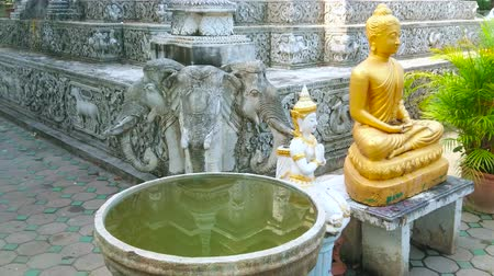trzy : The water bowl, golden Buddha Image and Devata deity guardian at the base of medieval chedi, decorated with wall statue of three-headed elephant, Wat Phan Waen (Pan Waen) temple, Chiang Mai, Thailand