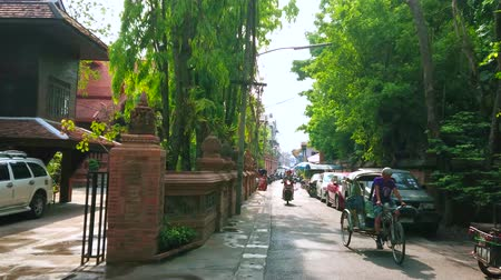 rickshaw : CHIANG MAI, THAILAND - MAY 4, 2019: The old rickshaw, bikes and cycles ride through the shady Pra Pok Clao road, on May 4 in Chiang Mai Stock Footage