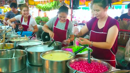 siamês : CHIANG MAI, THAILAND - MAY 4, 2019: Tanin market stall with wide range of Thai desserts - sticky puddings, rice and rice noodles in syrup or coconut milk, on May 4 in Chiang Mai Stock Footage