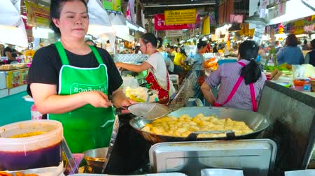mercado : CHIANG MAI, THAILAND - MAY 4, 2019: The seller of Tanin market stall cooks the tasty local puffs in deep fryer of the outdoor kitchen, on May 4 in Chiang Mai