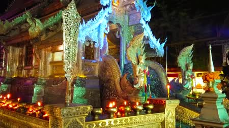 gravure : CHIANG MAI, THAILAND - MAY 4, 2019: The burning candles and aroma sticks in front of illuminated Silver Temple (Wat Sri Suphan) in the evening, on May 4 in Chiang Mai Stockvideo
