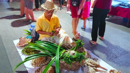 zabawka : CHIANG MAI, THAILAND - MAY 4, 2019: The artisan makes the flower bouquets from the palm leaves, sitting on the floor in Saturday Night Market in Wualai walking street, on May 4 in Chiang Mai