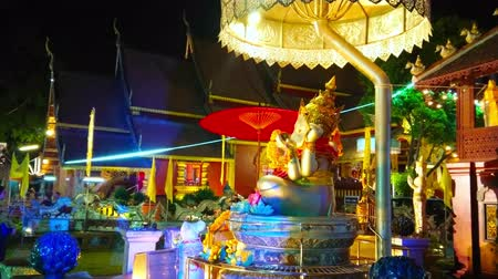 gravura : CHIANG MAI, THAILAND - MAY 4, 2019: The evening view on illuminated altar of Ganesha shrine with chatra umbrella, located in Silver Temple (Wat Sri Suphan), on May 4 in Chiang Mai