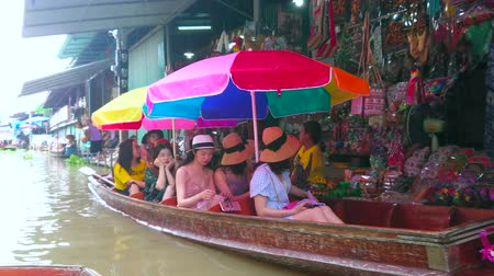 mercado : DAMNOEN SADUAK, THAILAND - MAY 13, 2019: Groups of tourists in wooden boats make shopping in souvenir stalls of Ton Khem floating market, on May 13 in Damnoen Saduak