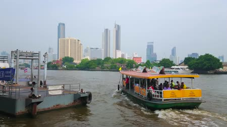 BANGKOK, THAILAND - MAY 15, 2019: The view on modern skyscrapers and boats, floating through the Chao Phraya river from the Ratchawong pier of Chinatown, on May 15 in Bangkok