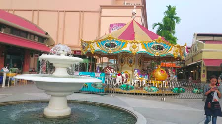 semt : BANGKOK, THAILAND - MAY 15, 2019: The classic carousel and small fountain in luna park of Asiatique The Riverfront shopping mall, on May 15 in Bangkok
