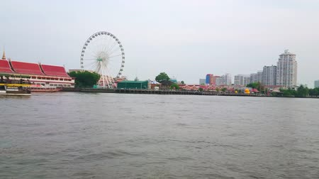 semt : BANGKOK, THAILAND - MAY 15, 2019: The trip through the Chao Phraya river with a view on Asiatique The Riverfront shopping mall, ferris wheel and market pavilions, on May 15 in Bangkok Stok Video