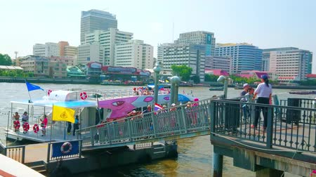kap : BANGKOK, THAILAND - APRIL 22, 2019: The large group of tourists gets off the ferry, arrived to the pier on Chao Phraya river, on April 22 in Bangkok