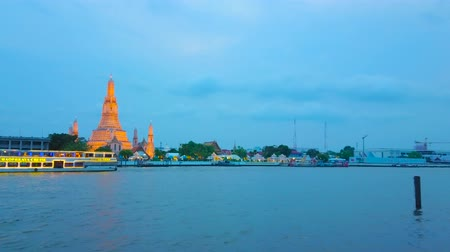 паром : BANGKOK, THAILAND - APRIL 22, 2019:  The pleasure boats and ferries on Chao Phraya river with a view on rising medieval Wat Arun Temple on blue hour, on April 22 in Bangkok