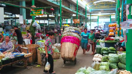 mercado : BANGKOK, THAILAND - APRIL 23, 2019: The narrow busy alley of central Wang Burapha Phirom agricultural market with walking visitors, sellers and porters, carrying different good, on April 23 in Bangkok
