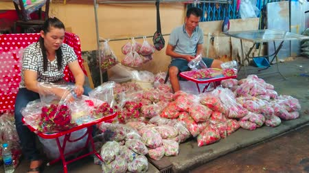 composição : BANGKOK, THAILAND - APRIL 23, 2019: The sellers pack the red rose petals to the plastic bags in small stall of Pak Khlong Talat flower market, on April 23 in Bangkok