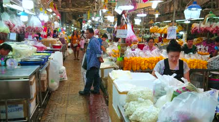 mercado : BANGKOK, THAILAND - APRIL 23, 2019: Alley of Pak Khlong Talat flower market with many shops and stalls, offering cut flowers, flower garlands, fragrant petals and floral decors, on April 23 in Bangkok