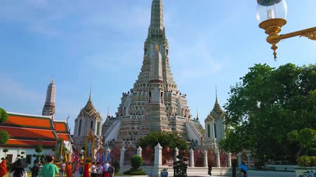 украшенный : BANGKOK, THAILAND - APRIL 23, 2019: Crowded square in front of stunning Wat Arun, richly decorated with tilling, sculptures of mythical creatures and faience relief ornaments, on April 23 in Bangkok