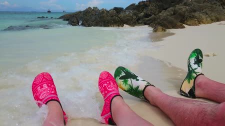 recife : PHUKET, THAILAND - MAY 1, 2019: Two couples of legs in bright aqua shoes, lying on the sand beach of Khai Nok island, on May 1 in Phuket Stock Footage