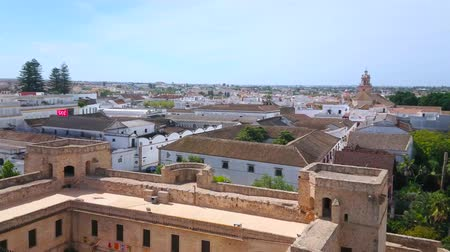 fabryka : SANLUCAR, SPAIN - SEPTEMBER 22, 2019: Panorama of Santiago Castle courtyard with banners and flags, roofs of old bodegas wineries and tall belfries of churches, on September 22 in Sanlucar Wideo