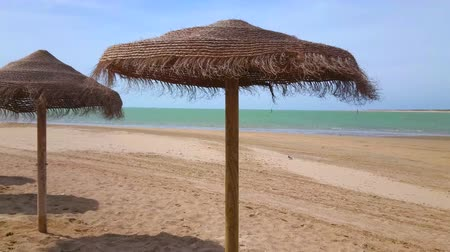szalma : The waving straw sunshades on the sandy Calzada beach, stretching along the mouth of Guadalquivir river, flowing to Atlantic Ocean, Sanlucar, Spain