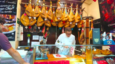 вылеченный : MALAGA, SPAIN - SEPTEMBER 26, 2019: Interior of gourmet store with hanging Jamon legs and seller, carving the slices from the whole Jamon Iberico leg, on September 26 in Malaga