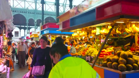bakkaliye : MALAGA, SPAIN - SEPTEMBER 28, 2019: The heaps of pineapples, mango, tomatoes, grape, banana bunches, other fresh fruits and vegetables in stalls of Atarazanas central market, on September 28 in Malaga Stok Video