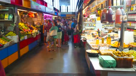 bakkaliye : MALAGA, SPAIN - SEPTEMBER 28, 2019: The alleyway in hall of Atarazanas central market with small stalls, offering pickles, fresh tropic fruits, dried nuts, drinks and spices, on September 28 in Malaga