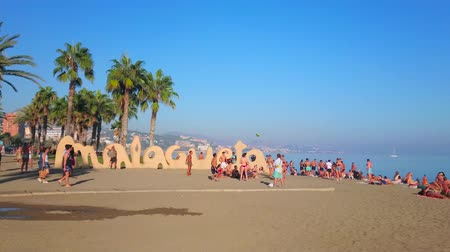 znamení : MALAGA, SPAIN - SEPTEMBER 28, 2019: The crowded Malagueta beach - one of the most popular city location, famous for comfort, beauty and Malagueta sign, on September 28 in Malaga