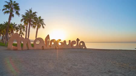 znamení : MALAGA, SPAIN - SEPTEMBER 28, 2019: The bright dawn sun shines through the Malagueta sign on the sand beach with tall palm trees and golden sea surface on the background, on September 28 in Malaga