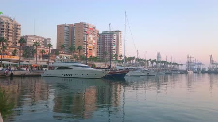 andalusie : MALAGA, SPAIN - SEPTEMBER 26, 2019: The sunset view on Muelle Uno pier with moored yachts, modern high rises, line of cafes, shops and walking tourists, on September 26 in Malaga