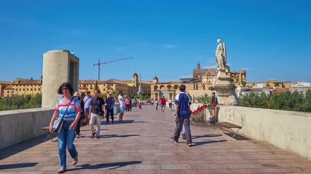 mór : CORDOBA, SPAIN - SEPTEMBER 30, 2019: Walk ancient Roman Bridge across Guadalquivir river with a view on Puerta del Puente gate, Mezquita-Catedral, Episcopal Palace, on September 30 in Cordoba Stock mozgókép